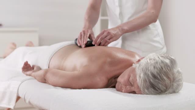 HD DOLLY: Senior Woman Having Hot Stone Spa Treatment video