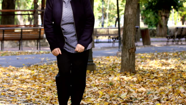 Senior woman having knee pain walking in park Senior woman walking in autumn park and having knee pain. Arthritis pain concept. The person comes in focus. knee stock videos & royalty-free footage