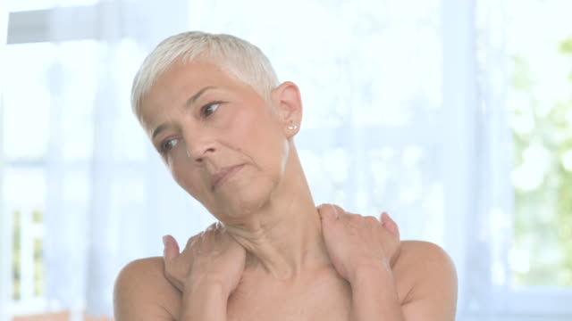 Senior woman having neck pain. Senior woman with short gray hair having neck pain. neck stock videos & royalty-free footage