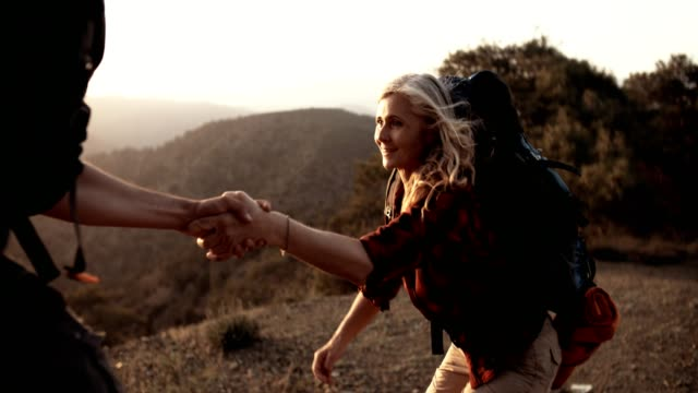 senior woman hiker holding helping hand to climb on mountain - trekking video stock e b–roll