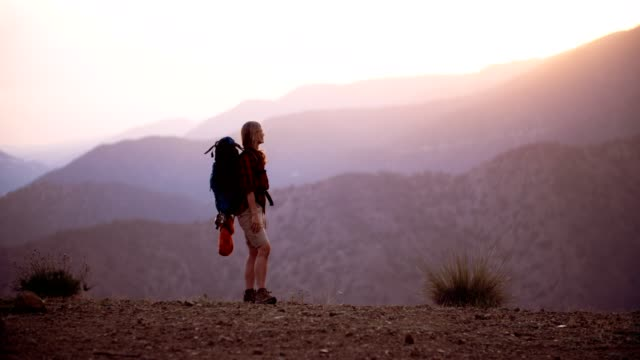 Senior woman hiker standing on mountain edge looking at view video