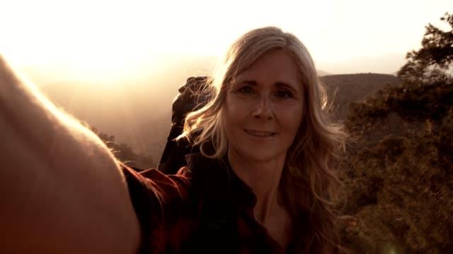 senior woman hiker taking selfies standing on mountain edge - woman portrait forest video stock e b–roll