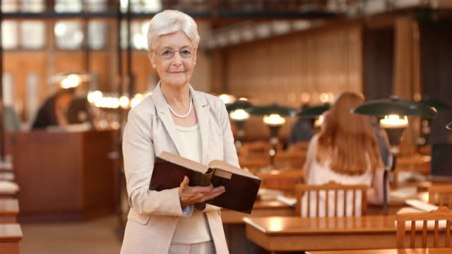 DS Senior woman holding a book standing in reading room video