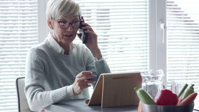 Senior woman holding a business card and talking on the phone Copy space video of cheerful senior woman sitting at the kitchen counter and smiling while talking on her mobile phone. She is also holding and looking at a business card while using phone. business card stock videos & royalty-free footage