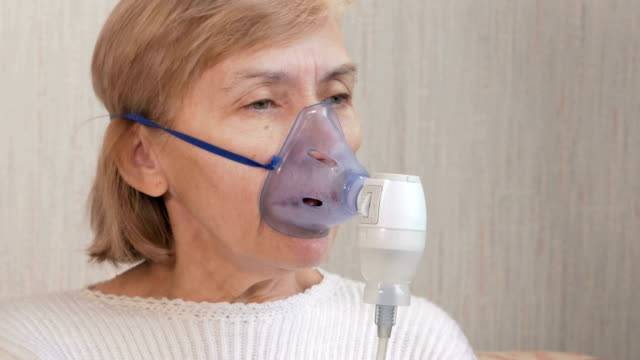 Senior woman holding a mask from an inhaler at home. Treats inflammation of the airways via nebulizer. Preventing asthma and cough video