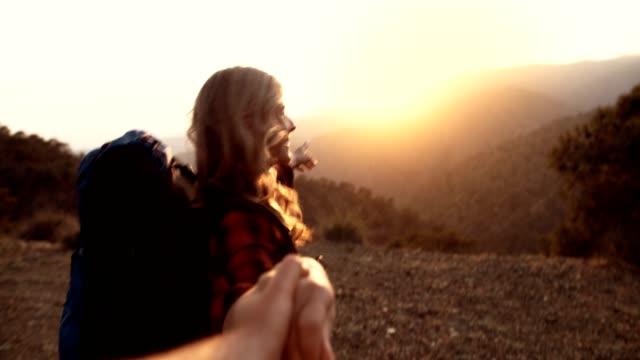 Senior woman holding partner's hand reaching mountain top at sunset