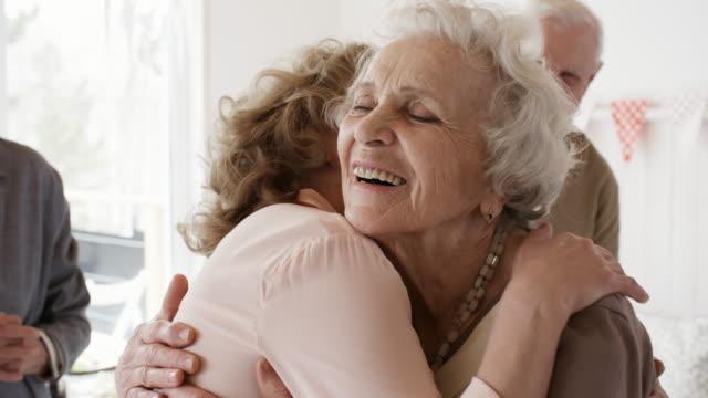 Senior Woman Hugging Guests at Home Party
