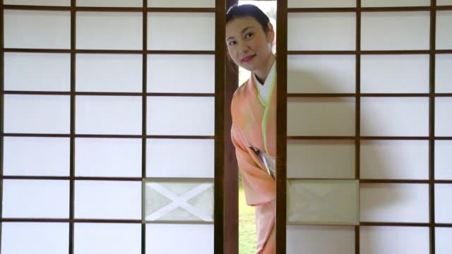 Senior woman in a Kimono opening a sliding door video