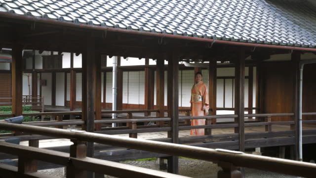 Senior woman in a Kimono taking a peaceful walk through a temple video