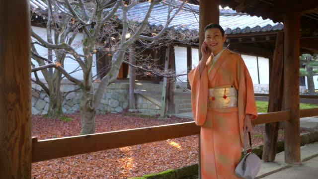 Senior woman in a Kimono walking through a temple talking on the phone video