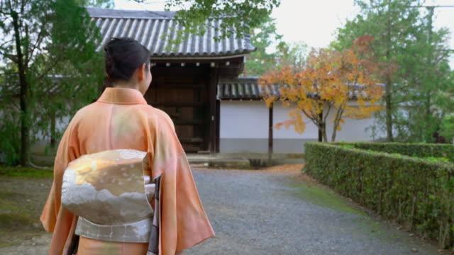 Senior woman in a Kimono walking through autumnal gardens video
