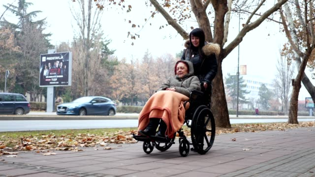 Senior woman in a wheelchair and a social worker enjoying their time together Senior woman in a wheelchair being pushed through the city by her daughter. pushing wheelchair stock videos & royalty-free footage