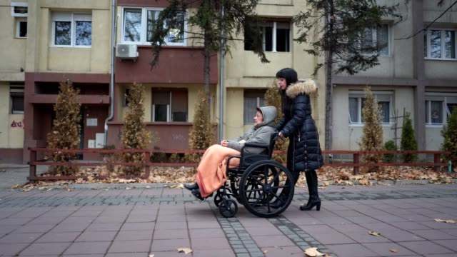 Senior woman in a wheelchair and her lovely daughter Senior woman in a wheelchair being pushed through the city by her daughter. sociology stock videos & royalty-free footage