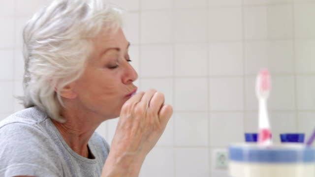 Senior Woman In Bathroom Brushing Teeth video