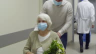 istock Senior Woman in Face Mask Leaving Hospital on Wheelchair with Help of Son 1268733435