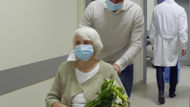 senior kvinna i ansiktsmask lämnar sjukhuset på rullstol med hjälp av son - hospital studio bildbanksvideor och videomaterial från bakom kulisserna