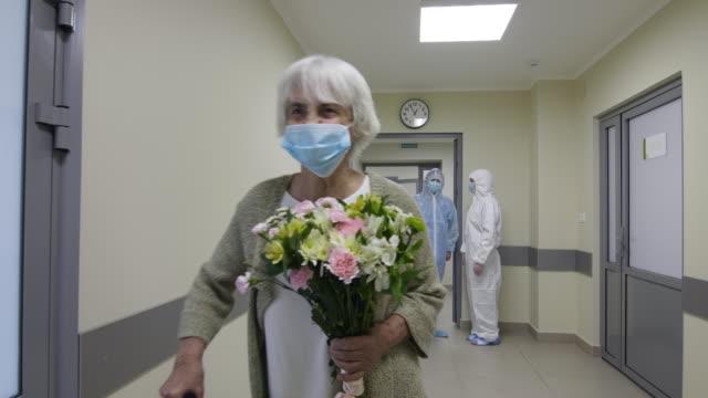 senior kvinna i ansiktsmask säger tack till läkare och lämnar sjukhuset - hospital studio bildbanksvideor och videomaterial från bakom kulisserna