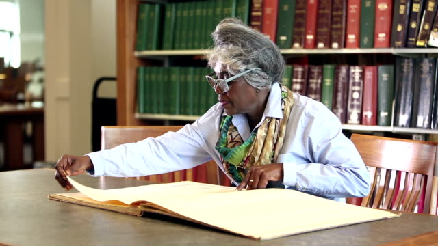 Senior woman in library examining an oversized book