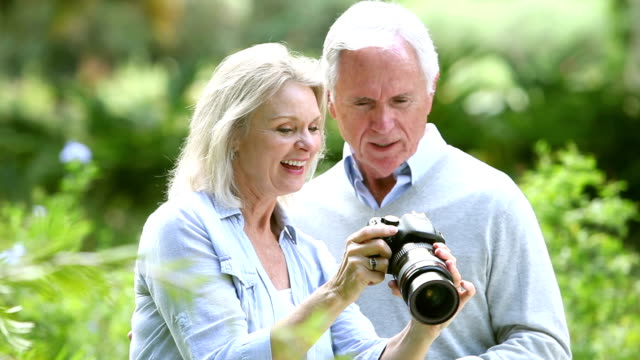 Senior woman in park taking photos, shows husband video