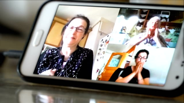 a senior woman in quarantine at home talking to her daughters - video call with family video stock e b–roll