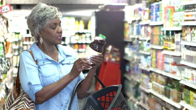 senior kvinna i stormarknad läsa mat etikett - ingrediens bildbanksvideor och videomaterial från bakom kulisserna