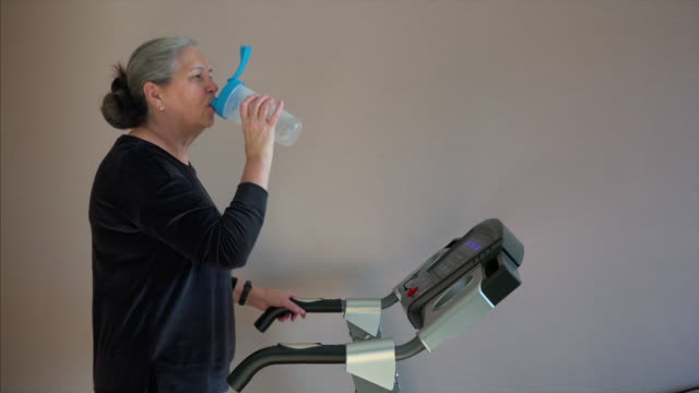 senior woman is drinking water from shaker bottle while walking on treadmill - runner rehab gym video stock e b–roll