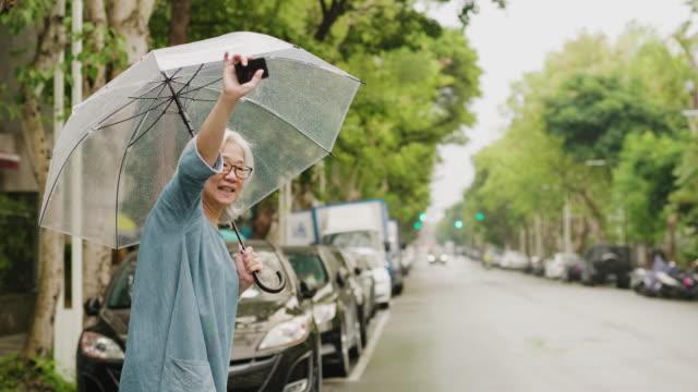 vídeos de stock, filmes e b-roll de a mulher sênior está esperando um táxi em um dia chuvoso na cidade - dividindo carro