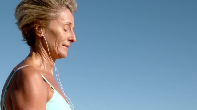 Senior woman jogging on a sunny day listening to music Senior woman jogging on a sunny day listening to music in slow motion 50 59 years stock videos & royalty-free footage