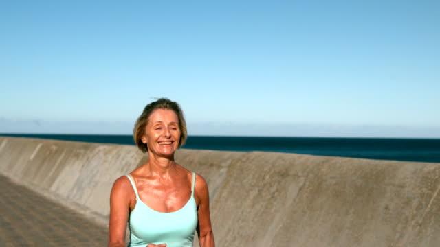 Senior woman jogging on a sunny day Senior woman jogging on a sunny day in slow motion 50 59 years stock videos & royalty-free footage