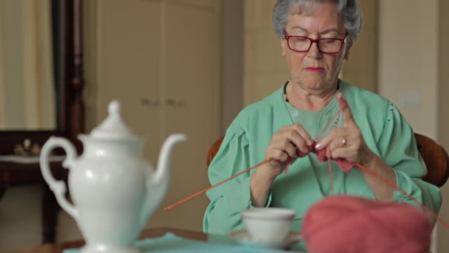 Senior woman knitting during tea time at home. video