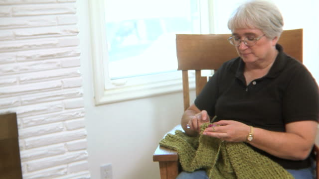 Senior woman knitting in rocking chair video