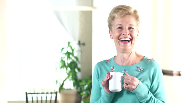Senior woman laughing, looking at camera, with coffee video