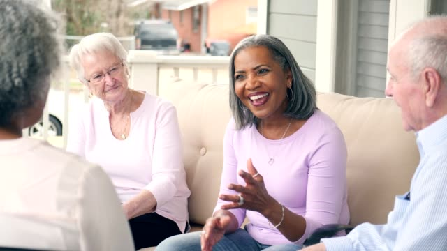 senior woman leads support group for senior adults - vicino video stock e b–roll