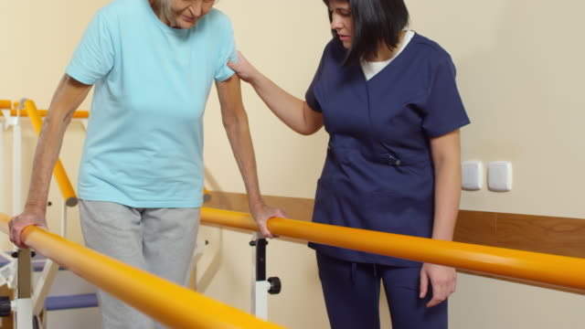 senior woman learning to walk with physiotherapist - physical therapy стоковые видео и кадры b-roll