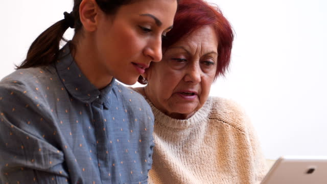 Senior woman leraning how to use digital tablet Granddaughter visiting her grandma in nursing home. She take care of her, talk with her, massage her. aging process stock videos & royalty-free footage