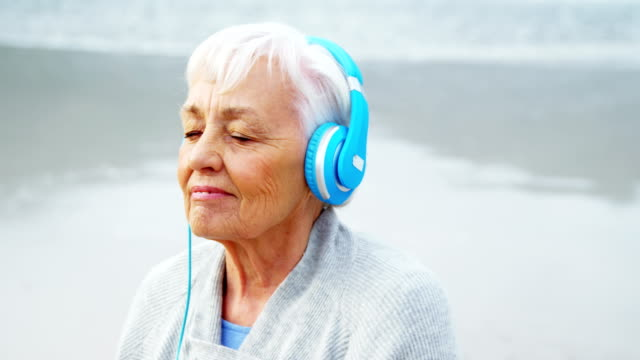Senior woman listening music on headphone on beach video
