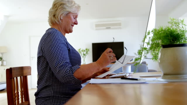 senior woman looking at document in home 4k - 60 69 anni video stock e b–roll