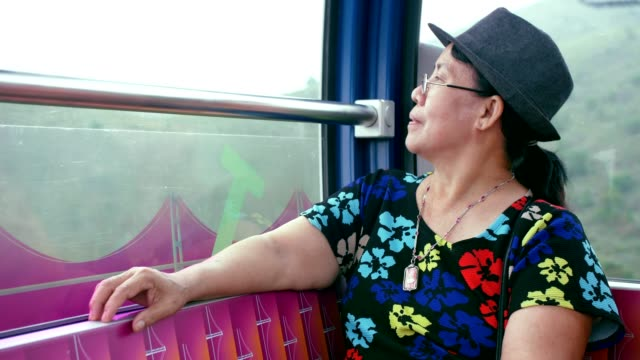 Senior woman looking at scenic view from cable car