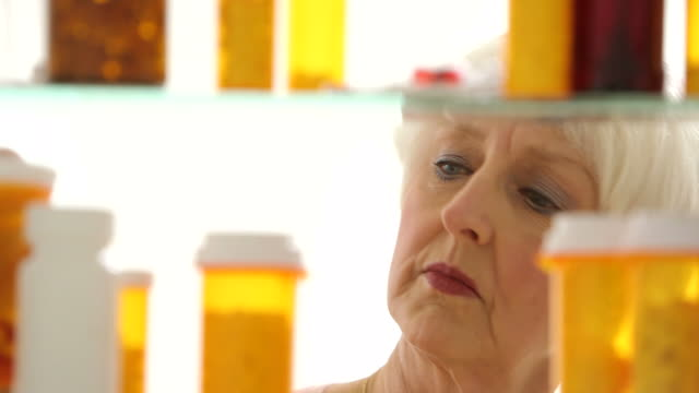 Senior woman looking for pills in medicine cabinet video
