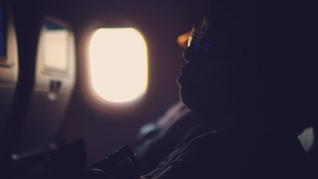 ältere frau suchen fenster des flugzeuges während des fluges - innerhalb stock-videos und b-roll-filmmaterial