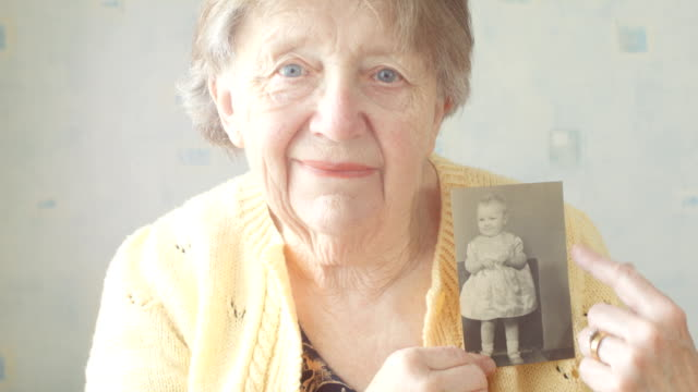 Senior woman looking through old photograph album video