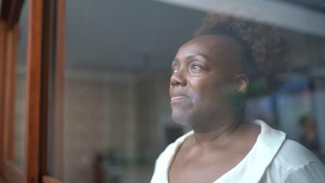 stockvideo's en b-roll-footage met hogere vrouw die door het venster kijkt - geloof