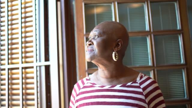 donna anziana che guarda attraverso la finestra contemplando e pensando a casa - distrarre lo sguardo video stock e b–roll