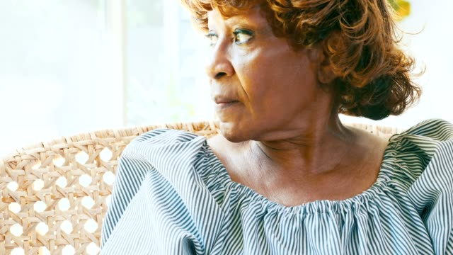Senior woman looks through window in her home