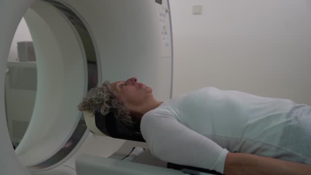 vídeos de stock e filmes b-roll de senior woman lying down on a flat bed scanner ready for a mri brain scan - instrumento para diagnóstico