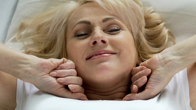 Senior woman lying in bed and stretching after her sleep, smiling, top view video