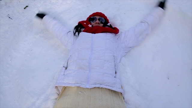 Senior woman makes a snow angel video