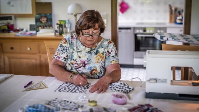 vídeos de stock, filmes e b-roll de mulher idosa fazendo máscaras antivírus em casa - hobbie