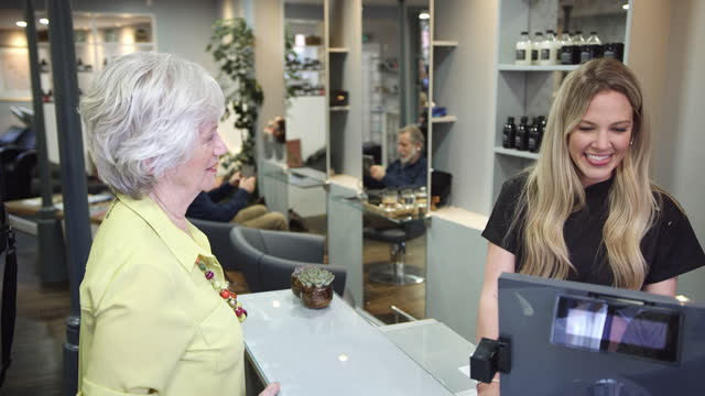 Senior Woman Making Contactless Payment To Stylist In Salon With Credit Card video