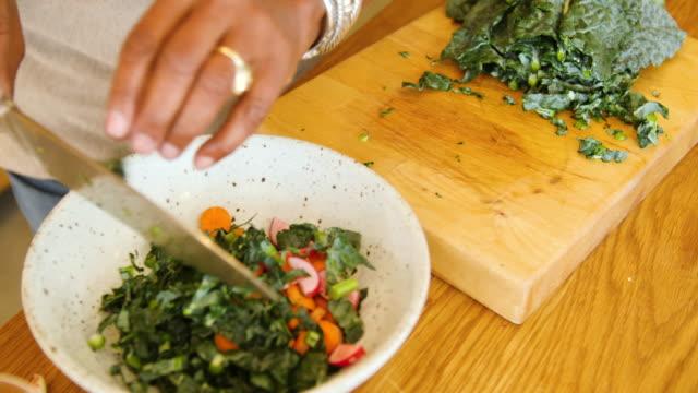 vídeos de stock, filmes e b-roll de mulher sênior que faz a salada vegetal da folha em casa - vegetarian meal